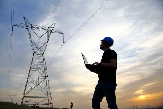 Technician operating laptop beside transmission tower